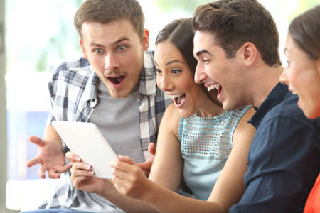 Vier verbaasde vrienden kijken media-inhoud samen in een tablet zittend op een sofa in de woonkamer thuis Stockfoto - 69040508