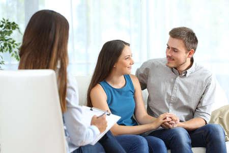 Pareja feliz escuchando a un consejero matrimonial y mirando el uno al otro durante el tratamiento en el hogar