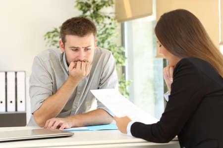 Hombre nervioso mirando cómo el entrevistador está leyendo su hoja de vida durante una entrevista de trabajo
