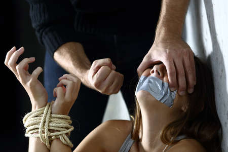 gagged: Terrified kidnapped woman being threatened by the fist of a kidnapper  Stock Photo