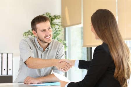 Gelukkig werknemer en baas handenschudden na een succesvol sollicitatiegesprek op het kantoor van