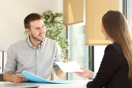 Man die een cv naar de interviewer in een sollicitatiegesprek in een Desktop op kantoor Stockfoto