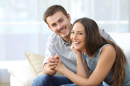 matrimonio feliz: matrimonio feliz posando y mirando a ti sentado en un sofá en la sala de estar en casa Foto de archivo