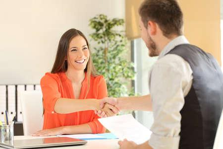 cerrando negocio: empleado feliz y el apretón de manos jefe después de una entrevista de trabajo exitosa en la oficina