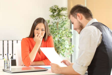 uninterested: Nervous woman looking at manager reading her resume during a job interview at office
