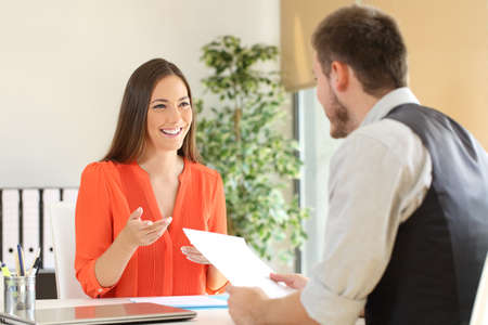 Confident woman and interviewer looking each other and talking during a job interview at office Stock Photo