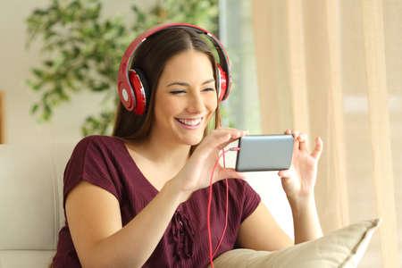 music lyrics: Hermosa chica ver videos en línea en un teléfono inteligente con auriculares sentado en un sofá en la sala de estar en casa Foto de archivo