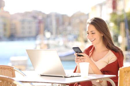 Chica utilizando un teléfono inteligente y un ordenador portátil en un bar o terraza del hotel con un puerto en el fondo
