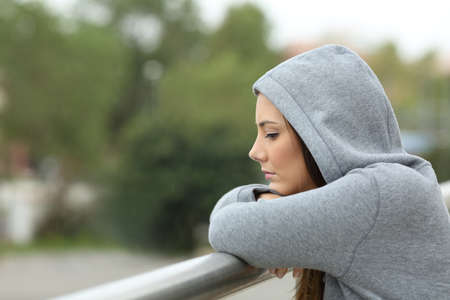 Vue latérale d'un adolescent célibataire triste regardant vers le bas dans un balcon de sa maison dans un jour pluvieux