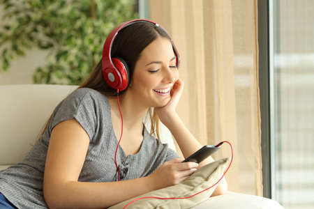 music lyrics: Happy girl listening music and selecting songs on a smart phone sitting in a couch at home