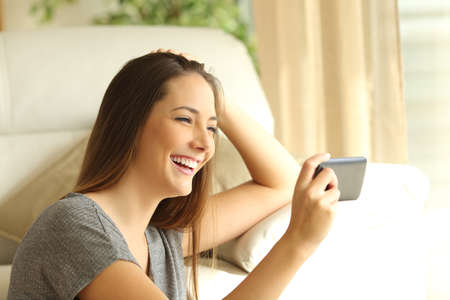Girl watching streaming video in a smart phone sitting on the floor of the living room at home near a window Stock Photo
