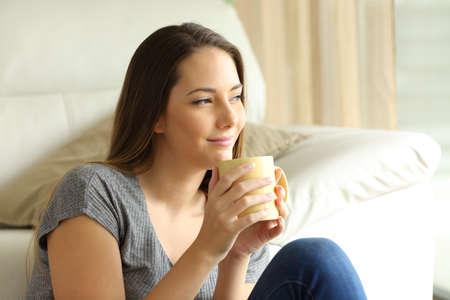 Détendue fille assise sur le sol en pensée avec une tasse de café en regardant à travers une fenêtre dans le salon