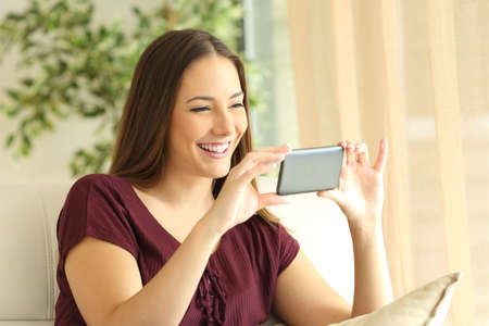 hands free device: Beautiful girl watching videos in a smart phone sitting on a sofa in the living room at home with a window in the background