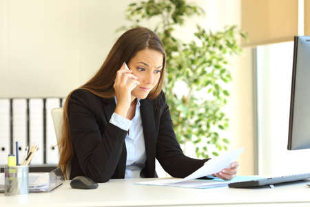 Upset businesswoman calling customer service about a budget or invoice problem at office