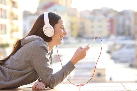 Vista lateral de una música que escucha adolescente en vacaciones tumbado en el suelo de la calle en un puerto con edificios en el fondo Foto de archivo