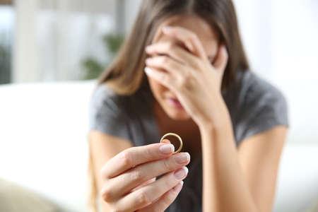 Detalle de una sola mujer triste divorcio después de lamentar que sostiene el anillo de bodas en un interior de la casa