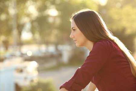 家のバルコニーで夕日見て距離と考えて 1 つの怒っている女性の側面図