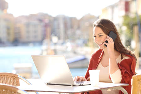 Girl using a laptop on line and calling customer service on mobile phone in a bar terrace with a port in the background