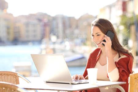 Meisje met behulp van een laptop op de lijn en klantenservice te bellen op de mobiele telefoon in een bar terras met een haven op de achtergrond