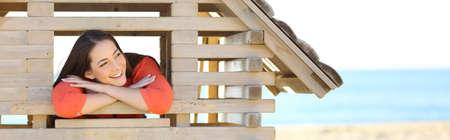 ビーチでのおもちゃの家の窓から見て彼女の夢の新しいアパートで考える女のフロントのパノラマ ビュー