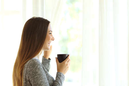 Side view of a single woman relaxing opening curtains and looking outside through window and enjoying a new day