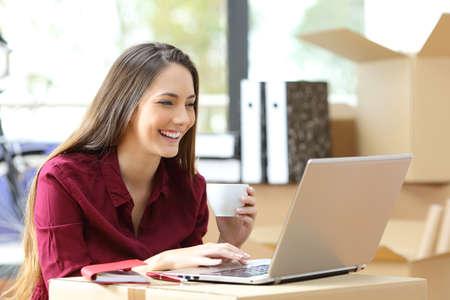 Mooie freelance werknemer die werkt met een laptop tijdens kantoorverhuizing met kartondozen op de achtergrond werken Stockfoto