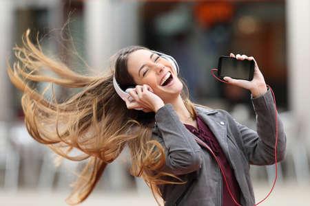 興奮して女の子ダンスとヘッドフォンと髪を移動するとストリートでスマート フォンの音楽を聴く 写真素材