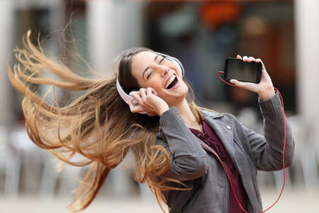 Excited girl dancing and listening music with headphones and smart phone in the street with hair moving 免版税图像