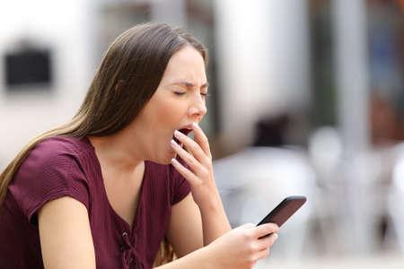 Mujer bostezo aburrido con el contenido de la línea que sostiene un teléfono móvil que se sienta en un banco en la calle