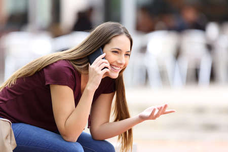 Happy girl calling on mobile phone looking away sitting on a bench in the street Stock Photo