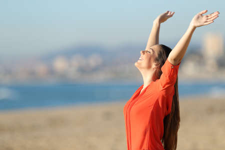 Side view portrait of a happy beautiful woman breathing and raising arms on the beach in a sunny day Stock Photo - 71129441