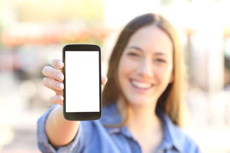 Vue de face d'une jeune fille heureuse montrant un écran de téléphone intelligent en blanc et en regardant vers la caméra dans la rue