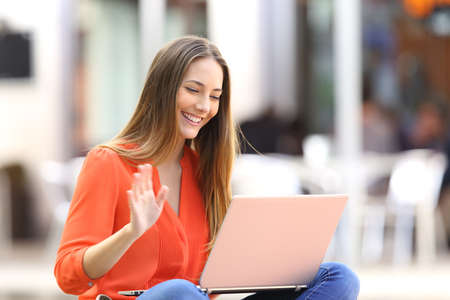 Happy woman talking on line in a video conference with a laptop sitting on a bench in the street Stock Photo