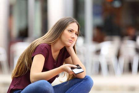 Sad girl attente pour un appel de téléphone mobile ou d'un message de son petit ami assis dans un banc à l'extérieur dans la rue avec un fond urbain