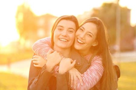 2 つの幸せな友人笑いとバック グラウンドで暖かい光で夕暮れ通りであなたを見てポーズの正面肖像画