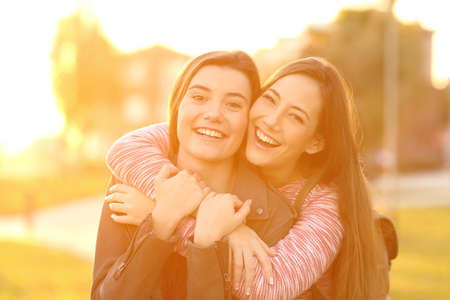 Front view portrait of two happy friends laughing and posing looking at you in the street at sunset with a warm light in the background