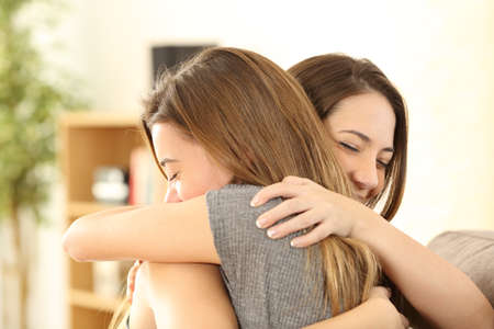 Happy girls embracing at home sitting on a couch in the living room at home 스톡 콘텐츠