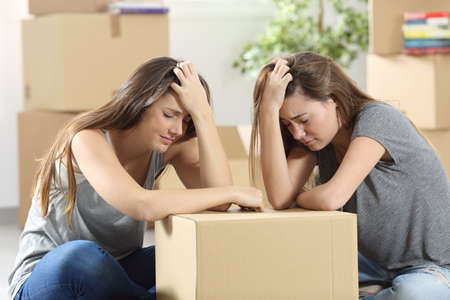 dispossession: Sad roommates moving house together after eviction sitting on the floor at home Stock Photo
