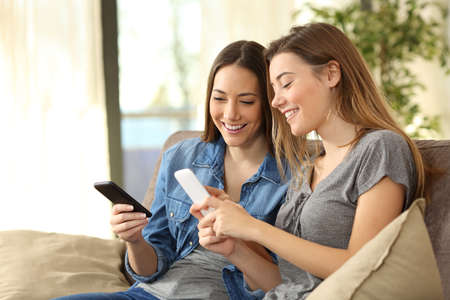 Due compagni di stanza utilizzando i loro telefoni intelligenti in linea a casa seduto su un divano nel soggiorno in casa Archivio Fotografico - 71228606