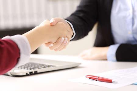 2 実業家手ハンド シェークの契約終了後の事務所背景と机に契約書に署名をクローズ アップ