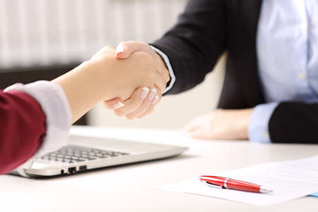 Close up of two businesswomen hands handshaking after closing a deal and signing contract in a desk with an office background 版權商用圖片