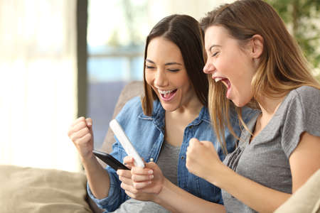 Two excited friends checking content on line in their smart phones sitting on a couch in the living room in a house interior