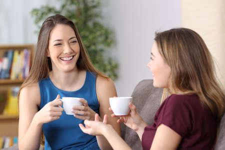 幸せな女の子の話と笑って、自宅の居間でソファーに座っていたコーヒー カップを保持しています。 写真素材