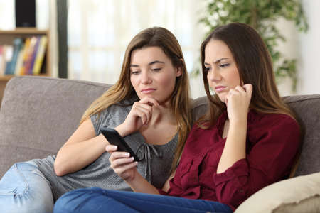 Two upset friends viewing on line content in a smart phone sitting on a sofa in the living room at home Banco de Imagens - 71228627