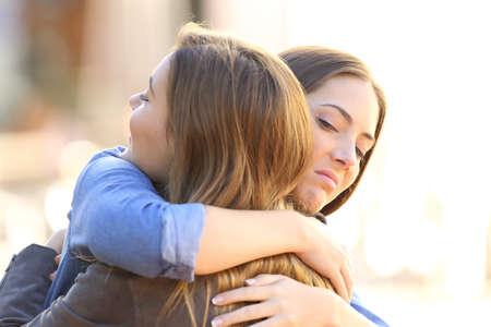 niña abrazando a un amigo hipócrita al aire libre en la calle Foto de archivo