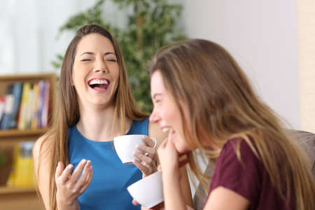 Portrait of two friends laughing loud together during a conversation sitting on a couch in the living room at home Foto de archivo