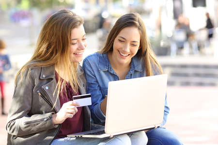 Two friends buying on line with credit card and a laptop sitting in a bench in the street with an urban background