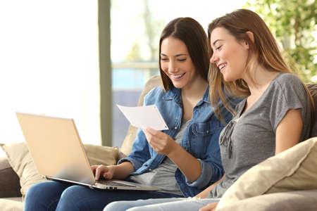 2 人のルームメイトが自宅の居間でソファに座ってノート パソコン ラインの銀行メールをチェック 写真素材