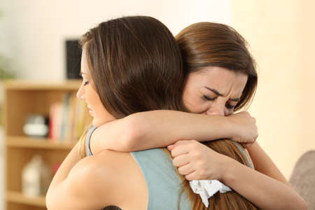 comfort room: Girl embracing to comfort to her sad best friend after break up sitting on a couch in the living room at home
