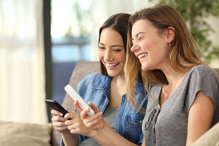 Two girls laughing watching media content on line in their smart phones sitting on a sofa in the living room at home
